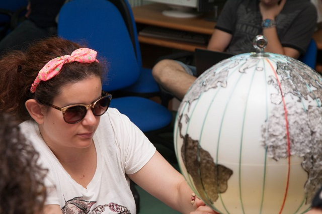Simona osserva il globo terrestre
